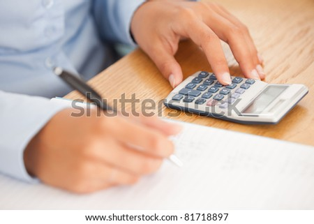 Feminine hands using a pen and a calculator in an office - stock photo