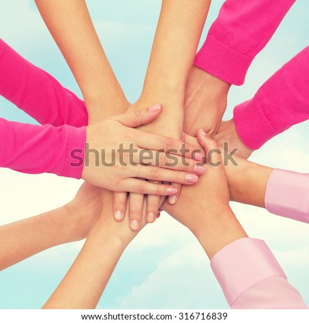 feminism, women power and breast cancer awareness concept - close up of women hands on top of each other over white background - stock photo