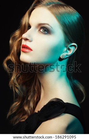 Femme fatal concept. Portrait of a beautiful young woman with ginger curly hair in black cocktail dress posing over black background. Perfect hairdo and great evening make-up. Diva (hollywood) style - stock photo