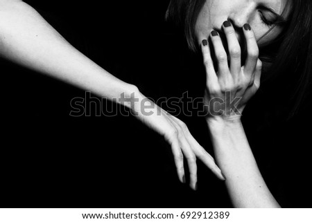 Femme fatale concept. Old classic movies actress style. Close up portrait of gorgeous young woman with beautiful hands over black background. Black and white, monochrome studio shot