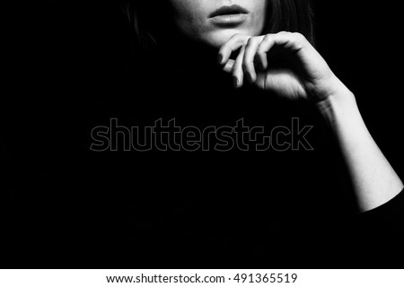 Femme fatale concept. Old classic movies actress style. Close up profile portrait of gorgeous young woman with beautiful hands over black background. Black and white studio shot Copy-space