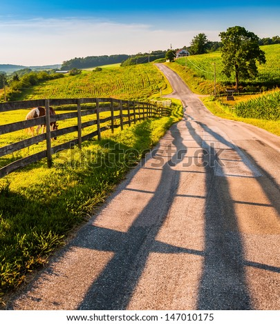 Fence and horses along a country backroad in rural York County, PA. - stock photo