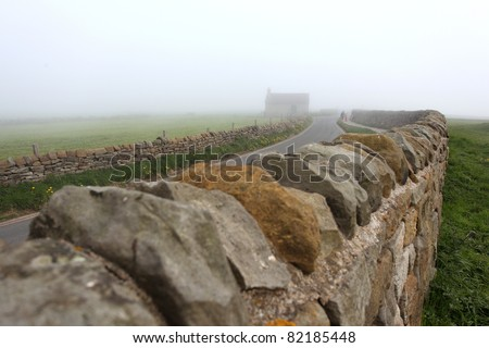 fence and road of Whitby Abbey castle shrouded in fog a ruined Benedictine abbey sited on Whitby's East Cliff in North Yorkshire on the north-east coast of England.UK
