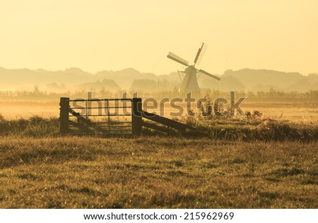 Fence and windmill in the Dutch countryside on a foggy day. - stock photo