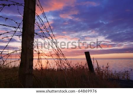 Fence, before a closely guarded, a naval base on the background of dawn. - stock photo