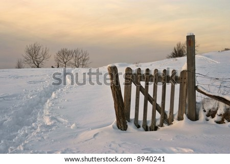 Fence, field ans snow : typical snowy lanscape in french jura, at dusk - stock photo
