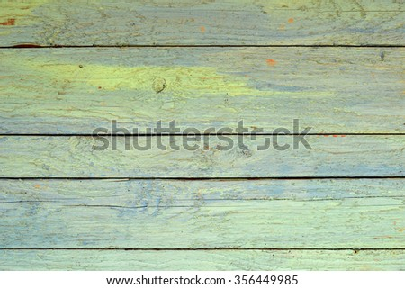 Fence from wooden green painted planks.