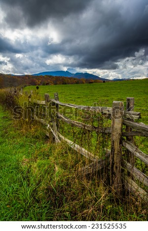 Fence in a farm field and view of Grandfather Mountain along the Blue Ridge Parkway in Moses Cone Park, North Carolina. - stock photo