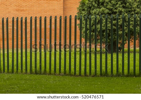 Fence in park with tree and wall of bricks