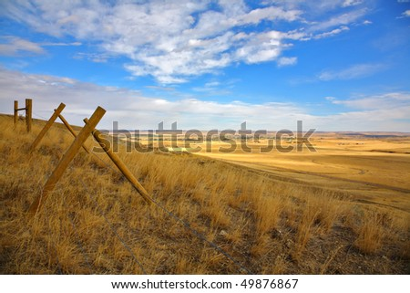 Fence in the American prairie. Serene autumn day - stock photo