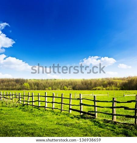 Fence in the green field under blue cloud sky. Beautiful landscape - stock photo