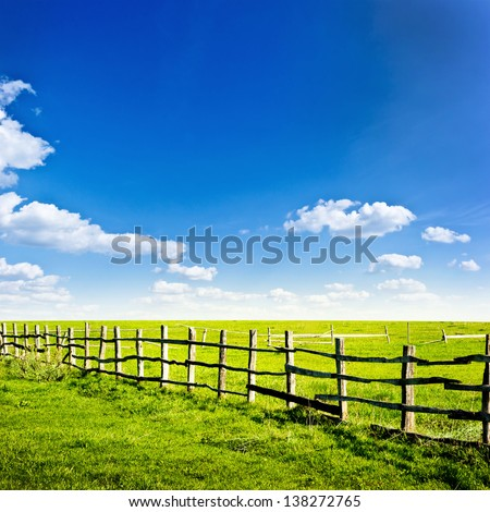 Fence in the green field under blue cloud sky. Beautiful landscape