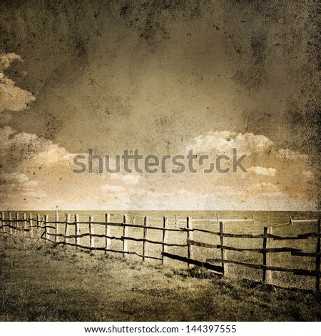 Fence in the green field under cloud sky. Beautiful grunge landscape background