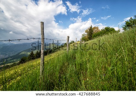 fence in the middle of the meadow in the mountains - stock photo