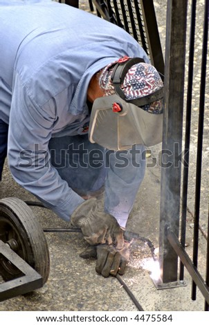 Fence installation worker welds a seal on a new fence post - stock photo