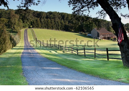 Fence lined road leading to farm and fields - stock photo