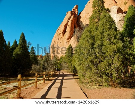 Fence lines the path that leads to the towering rocks - stock photo