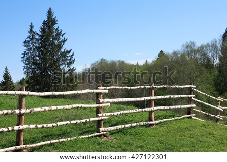 Fence made from wooden poles around field at summer - stock photo