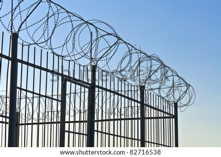 Fence of barbed wire. Against the blue sky - stock photo