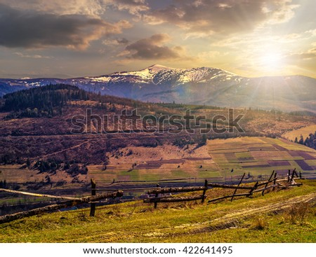 fence on the rural meadow in mountain region in spring time in evening light - stock photo