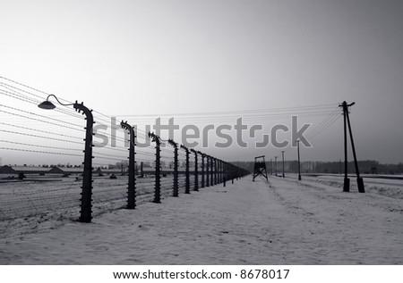 Fence surrounding Auschwitz / Birkenau camp - stock photo