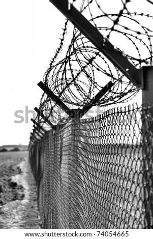 Fence with a barbed wire - stock photo