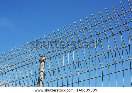 Fence with barb wire and blue sky