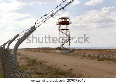 fence with barbed wire and watchtower - stock photo