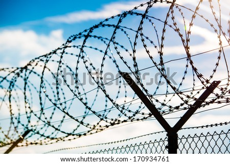 fence with barbed wire in front of great blue sky - concept for freedom, liberty or prison - stock photo