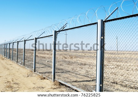 Fence with barbed wire on a background of blue sky - stock photo