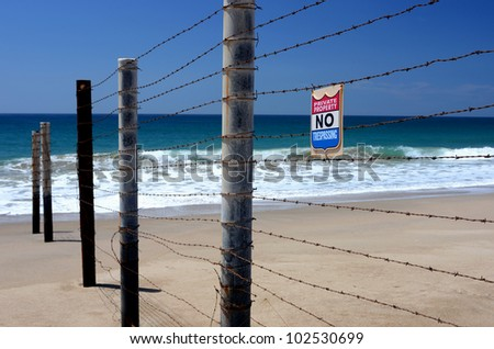Fence with barbed wire on a beautiful beach