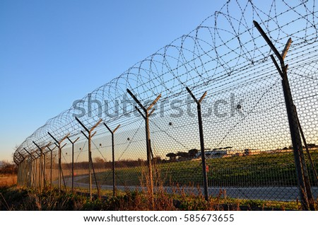 Fence with barbed wire on the sky at sunset background.