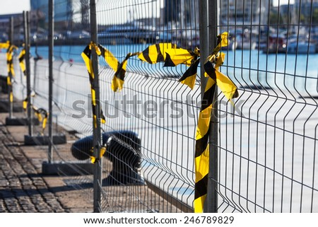 fence with ribbons on a construction site - stock photo