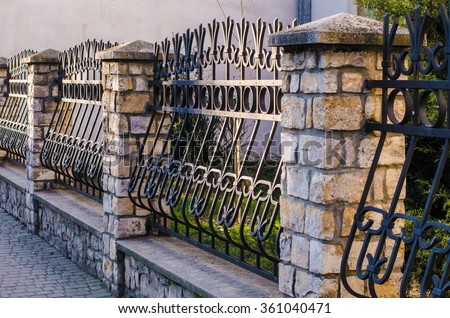 fence, wrought iron fence, forging and stone, wrought-iron ornaments,horizontal photo - stock photo