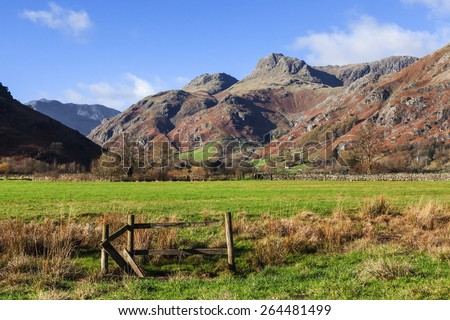 Fenced area in front of the Langdale Pikes. A small fenced area is seen in the foreground of this lovely view of the magnificent Langdale Pikes. - stock photo