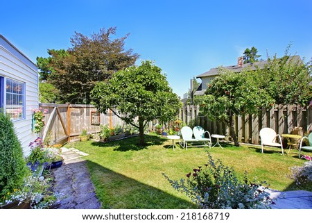 Fenced backyard garden with sitting area and apple trees. - stock photo