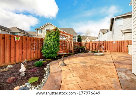 Fenced backyard with concrete tile floor deck and decorated flower bed - stock photo