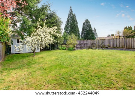 Fenced backyard with grass filled garden and small shed. View of blooming trees.