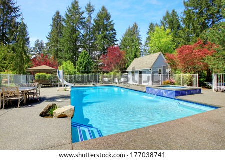 Fenced backyard with patio area, swimming pool and jacuzzi. Luxury real estate home. - stock photo
