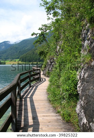 fenced wooden winding path between lake and rock - stock photo
