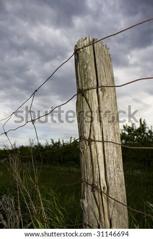 Fencepost under dramatic sky - stock photo