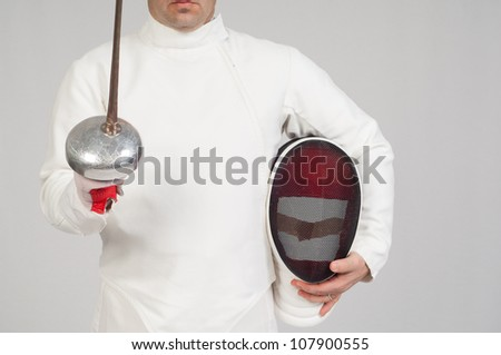 fencer athlete with sword and mask over grey background - stock photo