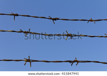Fencing. Fence with barbed wire. Let. Jail. Thorns. Block. A prisoner. Barbed wire under tension. Holocaust. Concentration camp. Prisoners. The tangle barb with blue sky. Barbed wire on blue sky. - stock photo