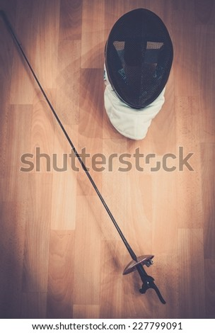 Fencing mask and epee on a floor  - stock photo