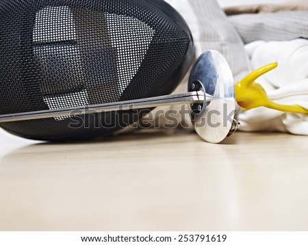 fencing mask and rapier on floor. - stock photo