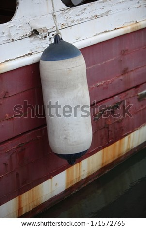 Fender hanging over the hull of a boat with rust stains and peeling paintwork - stock photo