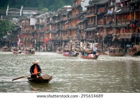 FENGHUANG, CHINA - JUNE 9 : Worker working clean on river every day in Fenghuang old town on June 9, 2015 in nghuang,Hunan Province China.This ancient town was added to the UNESCO World Heritage. - stock photo
