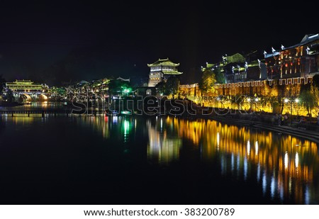 FENGHUANG, CHINA - SEPTEMBER 16, 2015: View of illuminated riverside houses in ancient town of Fenghuang known as Phoenix, China