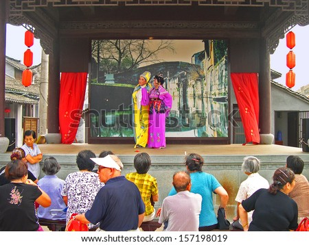 FENGJING, SHANGHAI, CHIN - SEPTEMBER 19: Actress performs a Chinese drama at a small theater. The village is a Shanghai tourist attraction with 100000 visitors year. September 19, 2004, Fengjing, China - stock photo