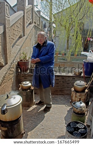 FENGJING, SHANGHAI, CHINA - MARCH 17: man cooking for a local restaurant. The ancient village is a Shanghai tourist attraction with 100000 visitors per year. March 17, 2010, Fengjing, China. - stock photo